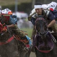 Mud flies during the Yoinori Keiba race, one of the events of the Soma Nomaoi festival recently held in Minamisoma, Fukushima Prefecture.   SHIHO FUKADA / BLOOMBERG