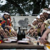 Men face off over sake for the Generals' Meeting held during the Soma Nomaoi festival in Minamisoma, Fukushima Prefecture.   SHIHO FUKADA / BLOOMBERG