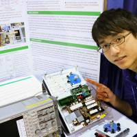 Takahiro Ichige shows off his power-saving controller during the Intel International Science and Engineering Fair in Phoenix in May. | COURTESY OF NIHON SCIENCE SERVICE / KYODO
