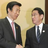 Foreign Minister Fumio Kishida is greeted by his South Korean counterpart, Yun Byung-se (left), in Vientiane on Monday. | KYODO
