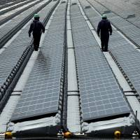Workers walk among the rows of solar panels at Kyocera Corp.'s floating solar power plant in Saka Sama Lake in Kasai, Hyogo Prefecture, in May 2015. | BLOOMBERG