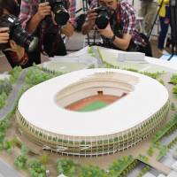 Photographers shoot a model of the new National Stadium on June 17 in Minato Ward, Tokyo. The model will be displayed at the Japan House set up for the Rio de Janeiro Olympics, where the Tokyo 2020 Games will be promoted. | KYODO
