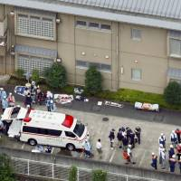 Ambulance personnel and staff at Tsukui Yamayuri En wait outside the care facility in Sagamihara, Kanagawa Prefecture, on Tuesday after a knife-wielding man broke in and killed at least 19 residents. | KYODO