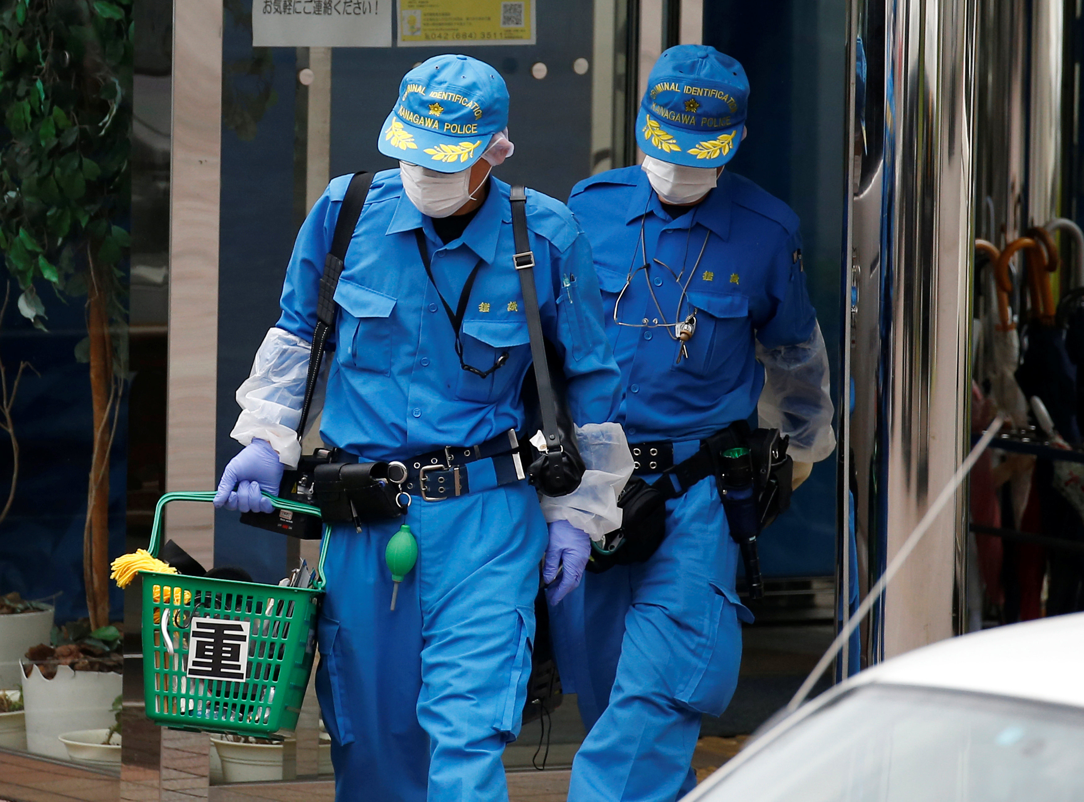 Police officers exit the Tsukui Yamayuri En care facility in Sagamihara, Kanagawa Prefecture, on Tuesday. | REUTERS