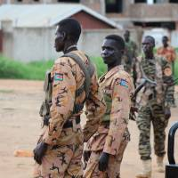 Police and soldiers stand guard along a street following renewed fighting in South Sudan's capital of Juba on Sunday. | REUTERS