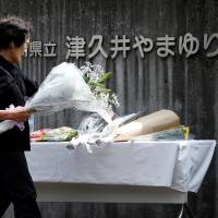 A mourner brings flowers on Wednesday to the care home where disabled residents were massacred a day earlier, in Sagamihara, Kanagawa Prefecture. | REUTERS