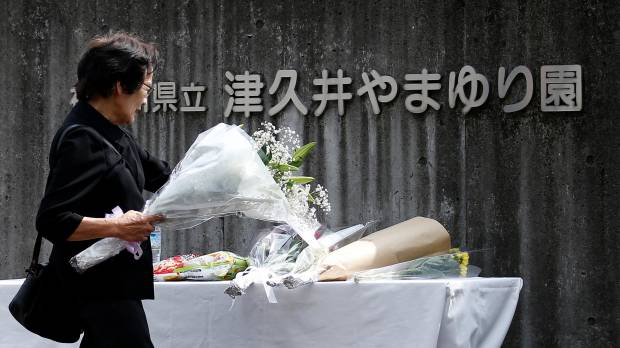 A mourner brings flowers on Wednesday to the care home where disabled residents were massacred a day earlier, in Sagamihara, Kanagawa Prefecture.