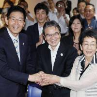 Akiko Mabuchi (right), director of the National Museum of Western Art, Ryohei Miyata (center), director of the Cultural Affairs Agency, and Taito Ward Mayor Yukuo Hayashi rejoice in Tokyo after the UNESCO World Heritage committee decided Sunday to add the museum to the World Heritage list. | KYODO