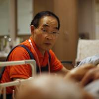 Caregiver Hiroshi Suzuki, 72, helps a resident at a nursing home operated by Care Twentyone Corp. in Tokyo on June 29. | BLOOMBERG