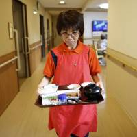 Caregiver Sonoe Kudo, 65, carries dinner to a resident at a nursing home operated by Care Twentyone Corp. in Tokyo on June 30.   BLOOMBERG