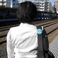 A woman wearing an anti-groping badge on her bag walks along a train station platform in Tokyo.  | DAISUKE KIKUCHI