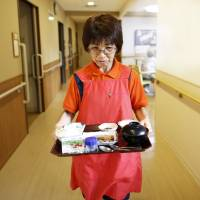 New responsibilities: Caregiver Sonoe Kudo carries dinner to a resident at a nursing home in Tokyo. Care for elderly relatives may become the legal duty of the family, reducing the government's own public-welfare responsibilities. | YUYA SHINO / BLOOMBERG