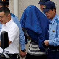 State of shock: Satoshi Uematsu (center, with a jacket over his head), who allegedly murdered 19 residents at a facility for people with disabilities, is escorted by police officers as he is taken from Tsukui police station in Sagamihara, Kanagawa Prefecture.   ISSEI KATO / REUTERS