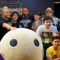 In the game: James Mielke (reaching out to the mascot) and John Davis (second to the right of Mielke) join other members of the BitSummit team for a group photo with some of this year's BitSummit Award winner. | JASON COSKREY