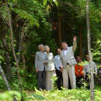 Back to basics: Emperor Akihito and Empress Michiko listen to C.W. Nicol as they walk together in the Afan Trust's woods in Shinano, Nagano Prefecture, in June. | COURTESY OF THE C.W. NICOL AFAN WOODLAND TRUST