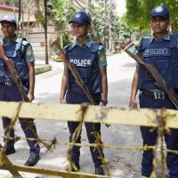 Heightened fear, heightened security: Police officers stand guard behind a roadblock near the Bangladesh restaurant where seven Japanese were murdered by militant jihadis on July 1. | KYODO