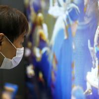 Pixel perfect: A visitor examines a 4K television at a tech exhibition in Tokyo. The difference  between full HD and 4K quality is only really noticeable on TV screens of at least 55 inches. | BLOOMBERG
