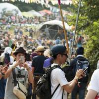 Pokemon, oh no: Festivalgoers take a break from the music to try out 'Pokemon Go,' but there were reportedly very few of the creatures at Fuji Rock. | JAMES HADFIELD