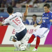 Yokohama F. Marinos' Takashi Kanai (right) and Nagoya Grampus' Lee Seung-hee vie for the ball during Saturday night's match at Nissan Stadium. The teams settled for a scoreless draw. | KYODO