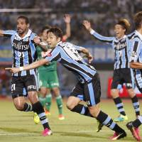 Frontale's Yu Kobayashi (center) begins to celebrate with his teammates after scoring against Albirex on Wednesday in Kawasaki. | KYODO