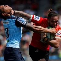 Sunwolves' Derek Carpenter (right) tries to fend off a tackle by Waratahs' Israel Folau in Tokyo on Saturday. | REUTERS