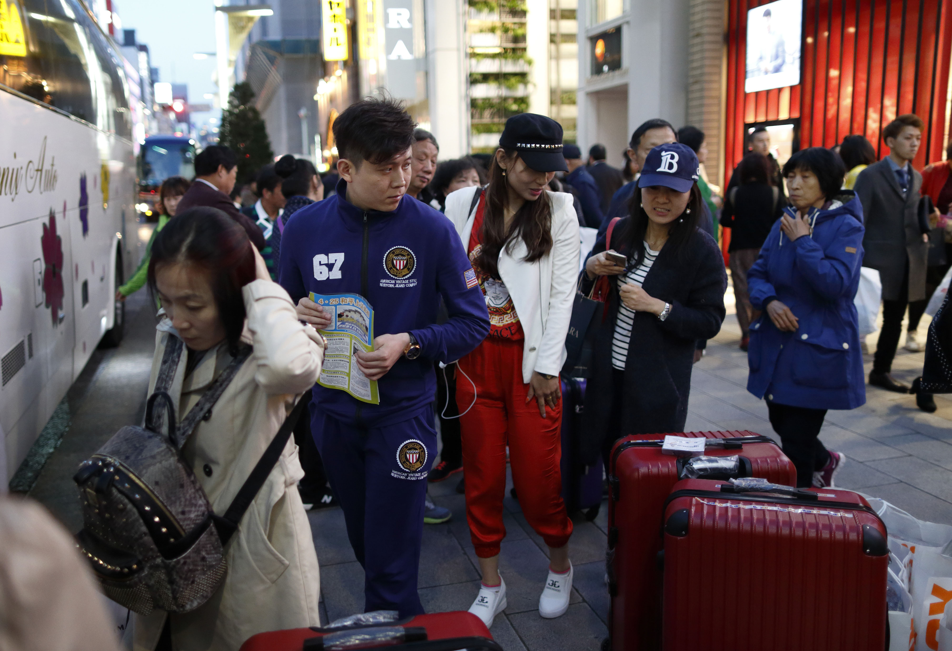 Chinese tourists board a tour bus in Tokyo's Ginza shopping district in April.   BLOOMBERG