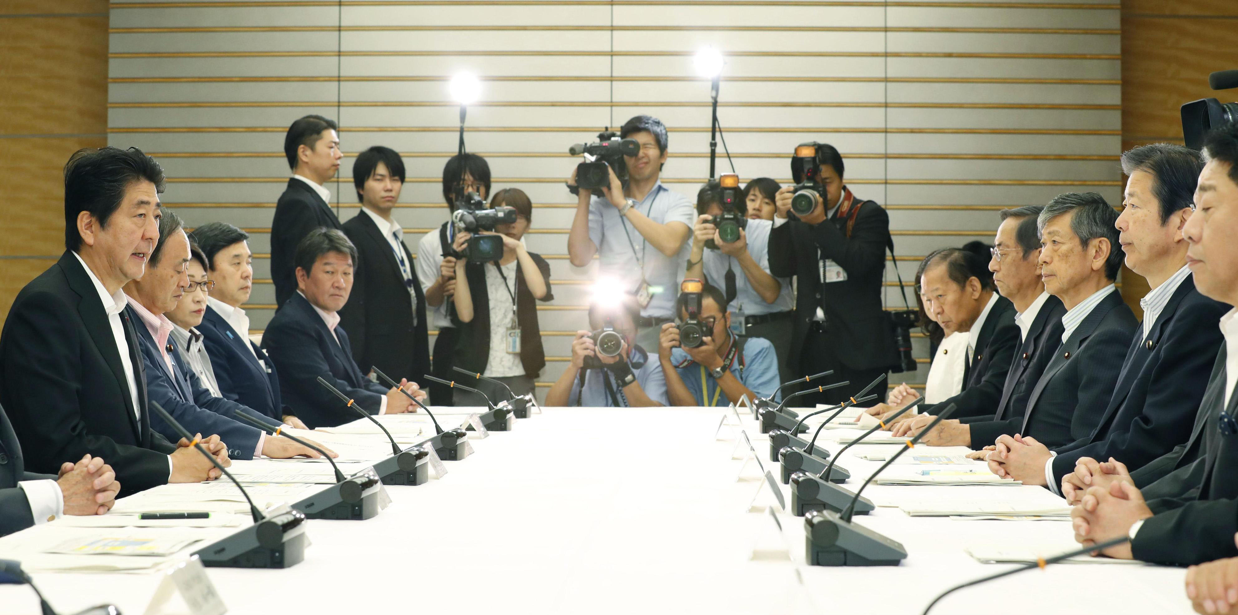 Prime Minister Shinzo Abe (far left) speaks at a policy meeting with coalition partner Komeito at the Prime Minister's Office on Tuesday. Sitting in front of him (second from right) is Komeito leader Natsuo Yamaguchi.   KYODO