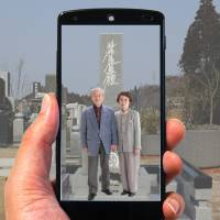 The app 'Spot message' shows video of a couple at a grave site.   COURTESY OF RYOSHIN SEKIZAI