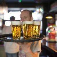 A barman carries a tray of Grolsch drafts, produced by SABMiller Plc, in a bar in Utrecht, Netherlands. Anheuser-Busch InBev NV has accepted Asahi Group Holdings Ltd.'s offer to buy the Peroni, Grolsch and Meantime beer brands. | BLOOMBERG