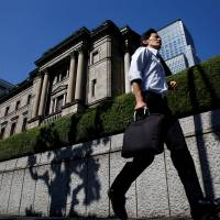 A man runs past the Bank of Japan building in Tokyo on July 29. | REUTERS