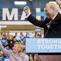 Berkshire Hathaway Chairman and CEO Warren Buffett cheers as he and Democratic presidential candidate Hillary Clinton arrive at a rally at Omaha North High Magnet School in Omaha, Nebraska, Monday. | AP