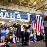 Democratic presidential candidate Hillary Clinton, accompanied by Berkshire Hathaway Chairman and CEO Warren Buffett, pauses while speaking at a rally at Omaha North High Magnet School in Omaha, Nebraska, Monday. | AP