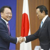 South Korean Strategy and Finance Minister Yoo Il-ho (left) and Finance Minister Taro Aso shake hands in Seoul on Saturday. | KYODO