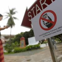A tourist walks near a sign reading  'No Pokemon Game Here' at the Tuol Sleng Genocide Museum, also known as the notorious security prison S-21, in Phnom Penh Wednesday. | REUTERS