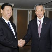 Xi Jinping (left), China's vice president at the time, shakes hands with Singapore Prime Minister Lee Hsien Loong at the Shangri-La Hotel in Singapore in November 2010. | BLOOMBERG