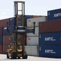 A forklift operates near stacked shipping containers at a port in the city of Shizuoka on June 27. Japan posted its largest current account surplus for a half-year period from January to June since the second half of 2007. | BLOOMBERG