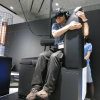A gamer wears a headset during a virtual reality battle from the safety of Gundam's palm, at VR Zone Project i Can in Tokyo's Odaiba district on Thursday. A heat lamp adds realism. | KAZUAKI NAGATA
