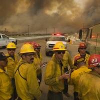 A U.S. Forest Service Hand crew looks for routes to aid in battling a wildfire near Highway 138 and Interstate 15 in California on Tuesday. | THE DAILY PRESS VIA AP