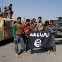 Afghan police pose for a photograph with an Islamic State flag after an operation in the Kot district of Jalalabad province east of Kabul on Aug. 1. | AP