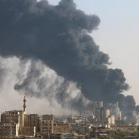A general view shows rising smoke from a Syrian regime controlled cement factory, in Aleppo, Syria, Tuesday. | REUTERS