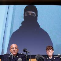 An image of Aaron Driver, a Canadian man killed by police Wednesday who had indicated he planned to carry out an imminent rush-hour attack on a major Canadian city, is projected on a screen during a news conference with Royal Canadian Mounted Police Deputy Commissioner Mike Cabana (left) and Assistant Commissioner Jennifer Strachan in Ottawa on Thursday. | REUTERS