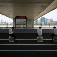 Men check their phones in Hangzhou, China, on Wednesday. | REUTERS