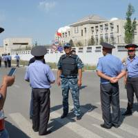 Kyrgyz police gather outside the Chinese embassy in Bishkek on Tuesdday. A van driven by a suicide bomber exploded after ramming through a gate at the embassy, wounding three people, authorities said. | AFP-JIJI