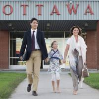 Canadian Prime Minister Justin Trudeau, his wife, Sophie Gregoire, and daughter, Ella-Grace, walk to board a government plane in Ottawa, Ontario, on Monday. Trudeau left for his first official visit to China. | AP