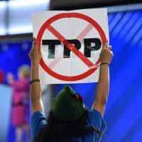 A delegate hoists an anti-TPP sign during the first day of the Democratic National Convention in Philadelphia on July 25. | AFP-JIJI