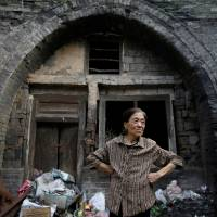 Li Yonghua, 65, stands in front of her damaged cave house in an area where land is sinking next to a coal mine in the village of Helin in China's Shanxi province on Aug. 2. | REUTERS
