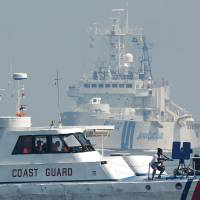 Philippine Coast Guard personnel act as mock pirates while a Japan Coast Guard ship steams toward their boat during a joint coast guard exercise in the waters off Manila Bay on July 13, a day after a U.N.-backed tribunal declared China has no 'historic rights' to the South China Sea. | AFP-JIJI