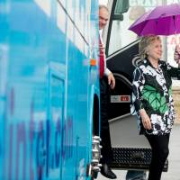 Democratic presidential candidate Hillary Clinton and Democratic vice presidential nominee Sen. Tim Kaine step off the campaign bus in light rain to visit Grandma's Cheese Barn in Ashland, Ohio, Sunday. | AP