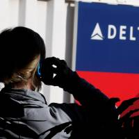A passenger talks on her phone at a Delta Airlines gate a day before the annual Thanksgiving Day holiday at the airport in Salt Lake City, Utah, on Nov. 21, 2012. | REUTERS