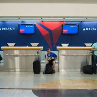 Passengers wait at Hartsfield-Jackson Atlanta International Airport on Aug. 8 after Delta flight cancellations and delays moved into their fourth day. | AP